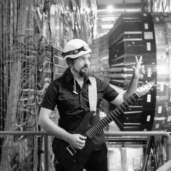 Physicist makes a peace sign next to the Large Hadron Collider at CERN