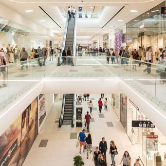 Consumers shopping in a large white shopping centre - consumer PR