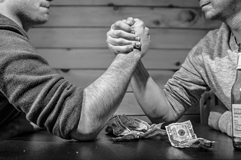 Men wrestling over money to illustrate sales web copy